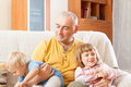 Dad and two daughters on sofa happy father with children in home interior Stock Photos