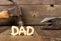 DAD wooden letters with tools in background against wood Royalty Free Stock Photo