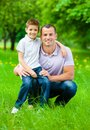 Daddy keeps son on the knee dad in park concept of happy family relations and carefree leisure time Stock Images