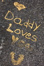 Daddy loves you the statement written on a boulder with golden paint Stock Images