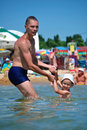 The daddy plays with the son in the sea Stock Photography