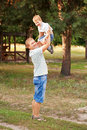 Daddy raising up the child happy father and son outdoors Royalty Free Stock Images