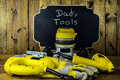 Dads tools electric power and work gloves with house fly on router in front of chalkboard reading on wood background Royalty Free Stock Photos