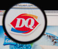 Dairy queen photo of homepage on a monitor screen through a magnifying glass Stock Image