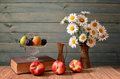 Daisy flowers and fresh peaches on a wodden table Stock Photo