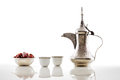 A dallah a metal pot for making arabic coffee with a bowl of dried dates is long spout designed specifically seen here and Royalty Free Stock Photography