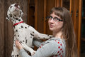 Dalmatian and girl the stands on hinder legs leaning on shoulders of the Stock Images