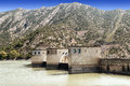 Dam in the mountains of the pyrenees surrounded by tree with house is spanish province lleida on a sunny day Stock Images