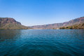 Dam wall waters valley water expanse blue sky and distant in neck Stock Photo