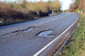 Damaged road with pot holes in it. Royalty Free Stock Photo