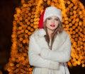 Dame à la mode utilisant le chapeau de noël et le manteau de fourrure blanc extérieurs portrait de jeune belle femme dans le Photo libre de droits