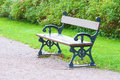 Damp bench empty made of cast iron and wood placed by gravel footpath with green grass and bushes behind Stock Images