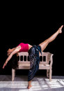 Dancer bending backwards with her legs pointing up in front of a bench Stock Images