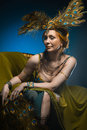 Dancer in exotic costume sits armchair on dark background Royalty Free Stock Photo