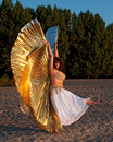 Dancer with Isis Wings on sand Royalty Free Stock Images