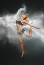 Dancer jumping into white powder young beautiful cloud against dark background Royalty Free Stock Photography