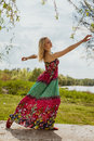 Dancing blonde romantic young woman in long dress beautiful bright on green meadow on warm sunny day spring Royalty Free Stock Photography