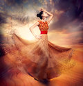Dancing fashion woman wearing blowing long chiffon dress Royalty Free Stock Image