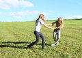 Dancing girls two happy little and twisting on green meadow with blue sky behind Stock Photo