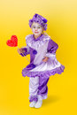 Dancing little clown girl with a heart shape lollipop for valentine s day or mothers day Royalty Free Stock Photos