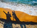 Dancing shadows of people on the sea sand and sea waves Royalty Free Stock Photo