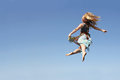 Dancing woman leaping through the air a happy young is blue sky background while smiling at camera Stock Photo