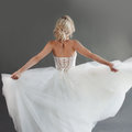 Dancing young bride in luxurious wedding dress. Pretty girl in white. Back, gray background Royalty Free Stock Photo