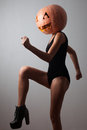 Dancing young woman with pumpkin on head Stock Photos