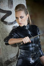 Danger girl with knife woman in sexy leather dress holding a in combat pose in old fabric ruins Stock Photo