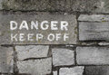 Danger keep off sign on stone Stock Image