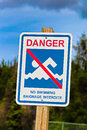 A danger, no swimming sign in both english and french Royalty Free Stock Photo
