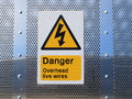 Danger overhead wires sign a showing complete with a black on yellow electrical flash Stock Photography