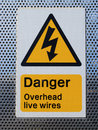 Danger overhead wires sign a showing complete with a black on yellow electrical flash Stock Photo