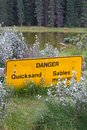 A danger quicksand sign with a pond in the background Royalty Free Stock Photo