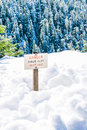Danger sheer cliff keep off sign on the edge of land cover with snow.. Royalty Free Stock Photo