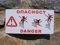 Danger sign photo of attached to a stone wall Royalty Free Stock Photo