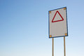Danger sign with red triangle tringle and four cautionary orange lights powered by solar energy on blue gradient sky background Royalty Free Stock Photography