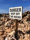 Danger sign on a rocky beach Royalty Free Stock Image