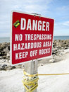 Danger sign a on a rocky beach which says no trespassing hazardous area keep off rocks Stock Photo