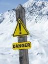 Danger sign yellow warning at edge of ski run Stock Images