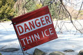 Danger thin ice a read sign that reads next to a frozen pond Royalty Free Stock Photo