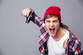 Dangerous agressive young man shouting and threatening with gun in checkered shirt red hat over grey background Royalty Free Stock Images
