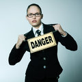 Dangerous business woman studio shot portrait of one caucasian young wearing a danger sign Royalty Free Stock Image
