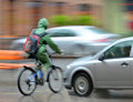 Dangerous city traffic situation with cyclist and car in the in motion blur Royalty Free Stock Image