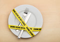 Dangerous food empty plate fork knife wrapped crime scene tape Royalty Free Stock Images
