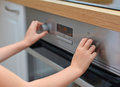 Dangerous situation in the kitchen child playing with electric oven Stock Photo