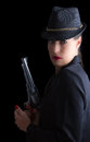 Dangerous woman in black with silver handgun and stylish hat Stock Photos