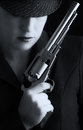 Dangerous woman in black with silver handgun and stylish hat artistic conversion Royalty Free Stock Photo
