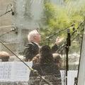 Daniel Barenboim conducting behind rain protection Royalty Free Stock Photo