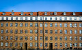 Danish apartment block a classic multistory in yellow brick stone with red tiled roof rectangular white dannebrog window frames Stock Images